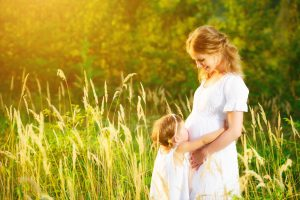 happy family, a pregnant mother and daughter little girl child in the summer meadow with yellow flowers