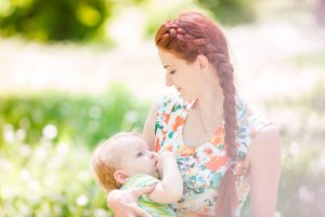 Beautiful happy mother breastfeeding her baby boy outdoor